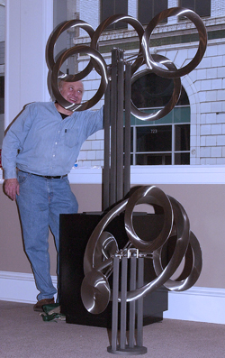 mobile_art --- Tom Brewitz of Stillwater, Min. positions his unique art form in the window of Galery Central Friday, Dec. 7, 2001. DV